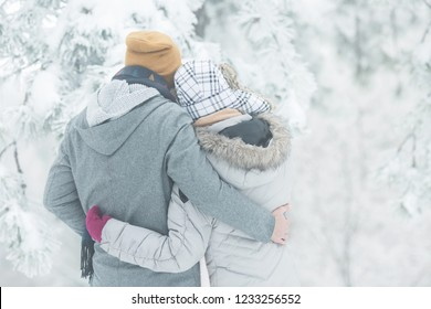 Young couple holding each other in snow outdoors