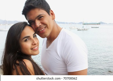 Young couple holding each other in front of the ocean