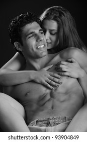 Young couple holding each other on black background