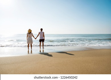 Young couple holding hand at the beach.
