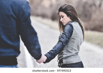 Young couple holding hands , braking up and leaving down the road concept