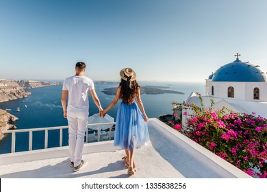 Young couple holding hands and enjoying view on Santorini Island, Greece