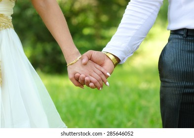 Young couple holding hands on the wedding in summer nature.