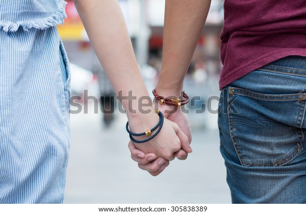 Young couple holding hands on the street together