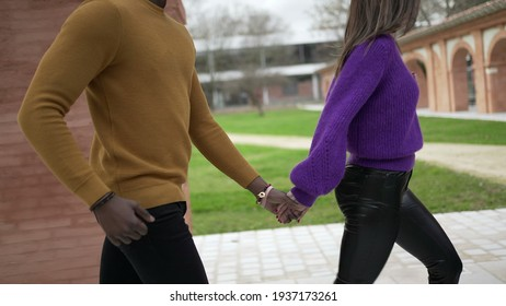 Young couple holding hands running together. Girlfriend leading boyfriend