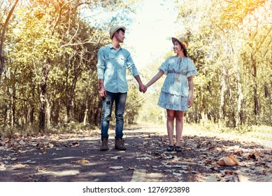 Young couple holding hands and walking through pathway on the street. Filtered image.