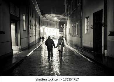 A young couple holding hands walking at night in old town street, cobbled street wet from rain, autumn evening, black and white. Visible only silhouettes of models, there is no need model release.