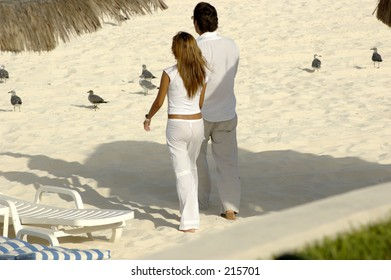 Young couple holding hands and walking along the beach towards the ocean.