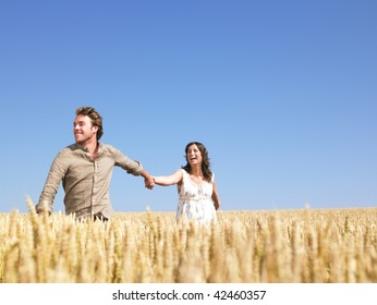 A young couple holding hands and walking through wheat field. Horizontally framed shot.