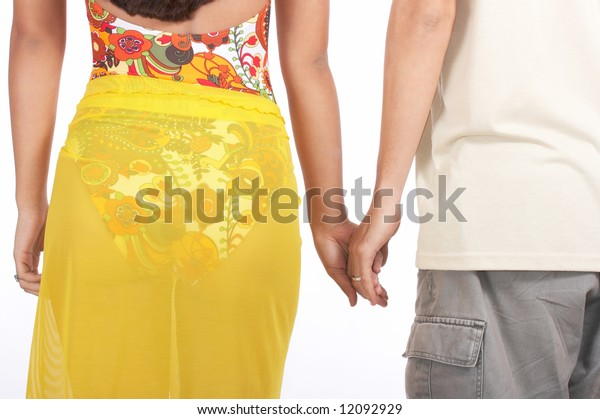 young couple holding hands walking on the beach