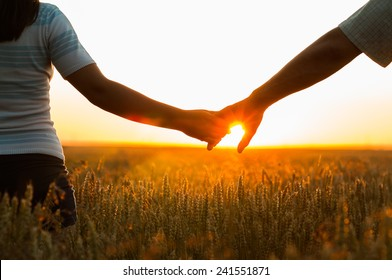 Young couple holding hands in the wheat field on sunny summer day.