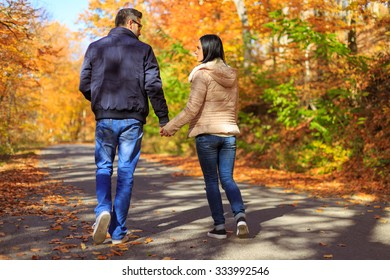 Young couple holding hands while taking a walk in nature