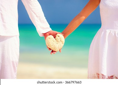 young couple holding heart shape stone on tropical beach