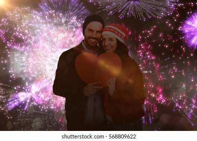 Young couple holding heart shape paper against colourful fireworks exploding on black background