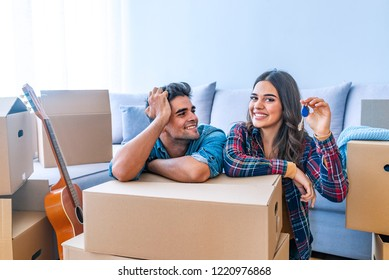 Young couple holding key in hand. Our home will be filled with so much love. The keys to our new home. Couple holding a house key in their new home. Happy attractive young couple is moving