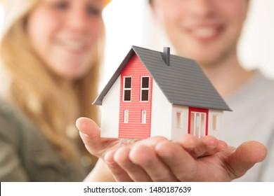 A young couple is holding a model house in hand, new home