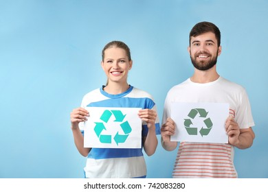 Young couple holding paper sheet with recycling symbol on color background