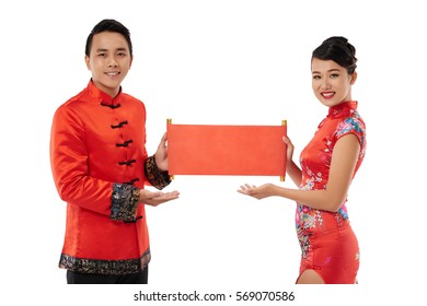 Young couple holding red scroll for couplets with best wishes for coming year