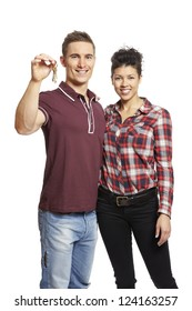 Young couple holding set of house keys on white background smiling