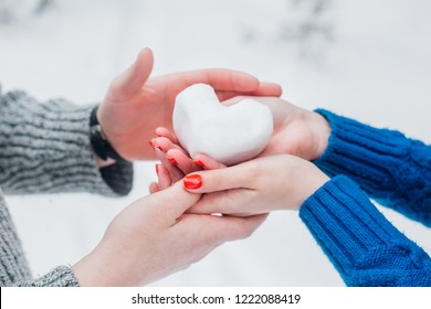 young couple holding snow heart. Hands in knitted mittens with heart of snow in winter day. Love concept. Valentine day background.