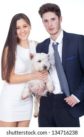 young couple holding a white dog