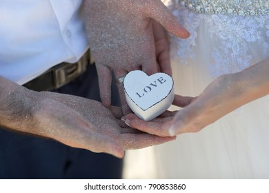 young couple holding white wooden box with love message