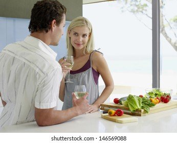 Young couple holding wineglasses at kitchen counter