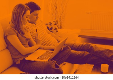 young couple at home with  modern livingroom indoor working on laptop on house finance and planing duo tone