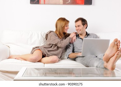 Young couple at home on white sofa with notebook