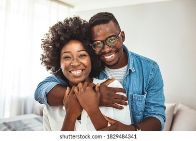 Young couple at home. Portrait of happy couple looking at camera against gray background. Enjoying every minute together. Cropped portrait of a man affectionately embracing his wife at home