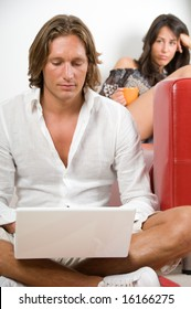 Young couple at home, she is sitting on the sofa and he works with laptop