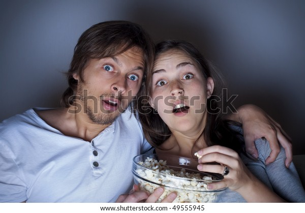 Young couple at home watching a movie with popcorn