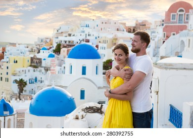 young couple honeymoon on the most romantic island Santorini, Greece. Sunset in the city Oia
