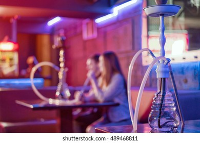 Young couple in a hookah bar. The background is blurred. In the foreground is a large hookah.