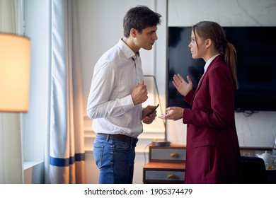 Young couple at the hotel room discussing troubles at their business trip for a new deal. Hotel, business, people