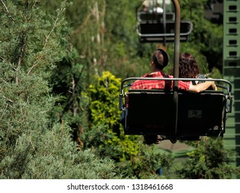 Young couple huddled outdoors on a chair lift. Excursion in the forest.