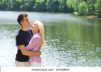 Young couple hug at lake