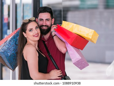 young couple hugging each other at the shopping mall on a sunny day