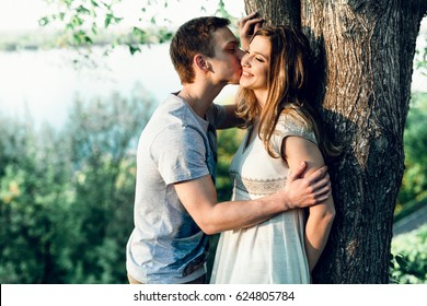 Young couple hugging elbow on tree trunk