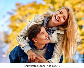 Young couple hugging and flirting in park and looking away. Yellow autumn park background.