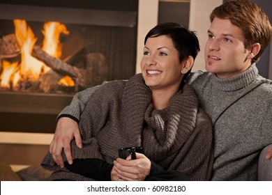 Young couple hugging in front of fireplace at home, looking away, smiling.