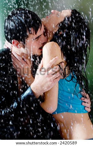 young couple hugging kissing under rain stock photo edit now