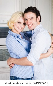 young couple hugging in the kitchen at home