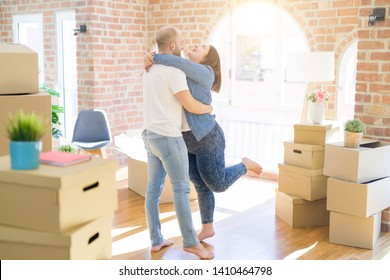 Young couple hugging in love arround carboard boxes at new home, celebrating very happy moving to new apartment