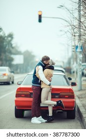 Young couple hugging near their car.