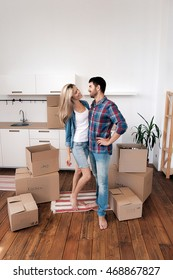 Young couple hugging in new kitchen with boxes with home things.Copy space