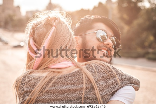 Young couple is hugging on the street under the sunlight.