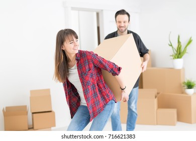 A young couple is introduced into a new apartment. They carry the boxes in your new home. They are happy and joyful.