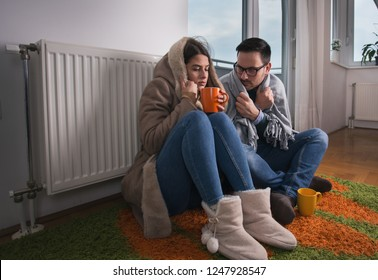 Young couple in jacket and covered with blanket sitting on floor beside radiator and trying to warm up