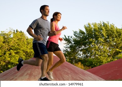 A young couple jog around a park with each other. - horizontally framed